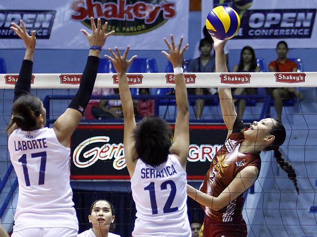 Maria Tabaquero of cagayan spikes the ball against two navy players.KC Cruz